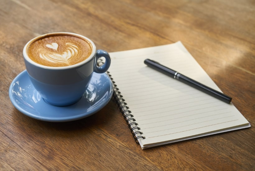 notebook with blue mug of latte