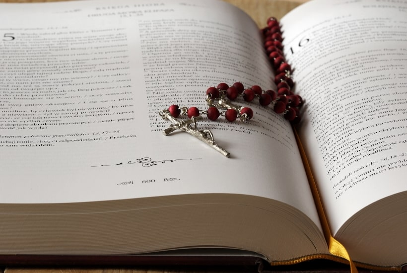 bible open with a rose colored rosary on top