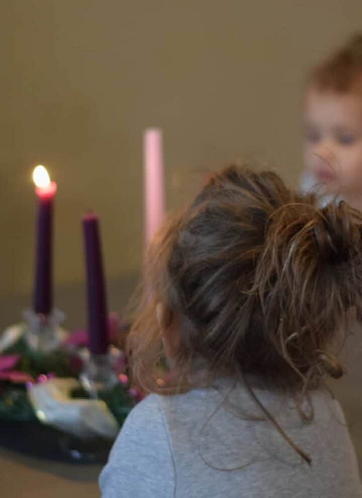 children looking at lit up advent wreath