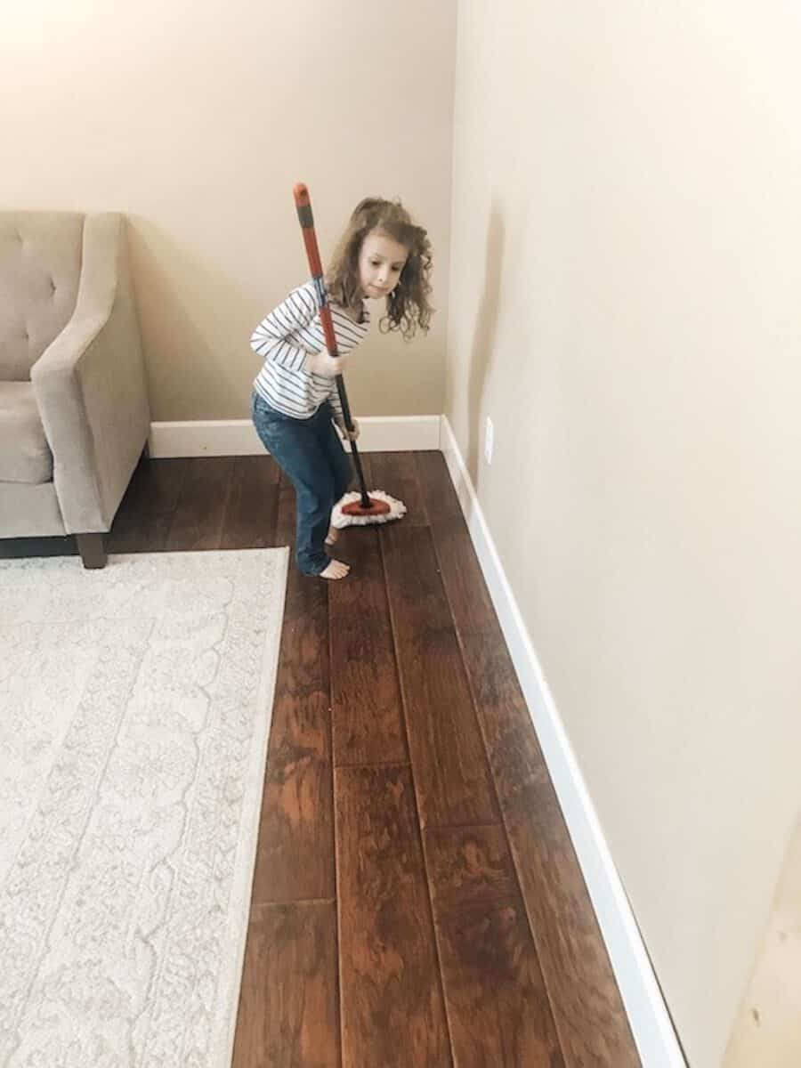 child working on chores and cleaning the floor
