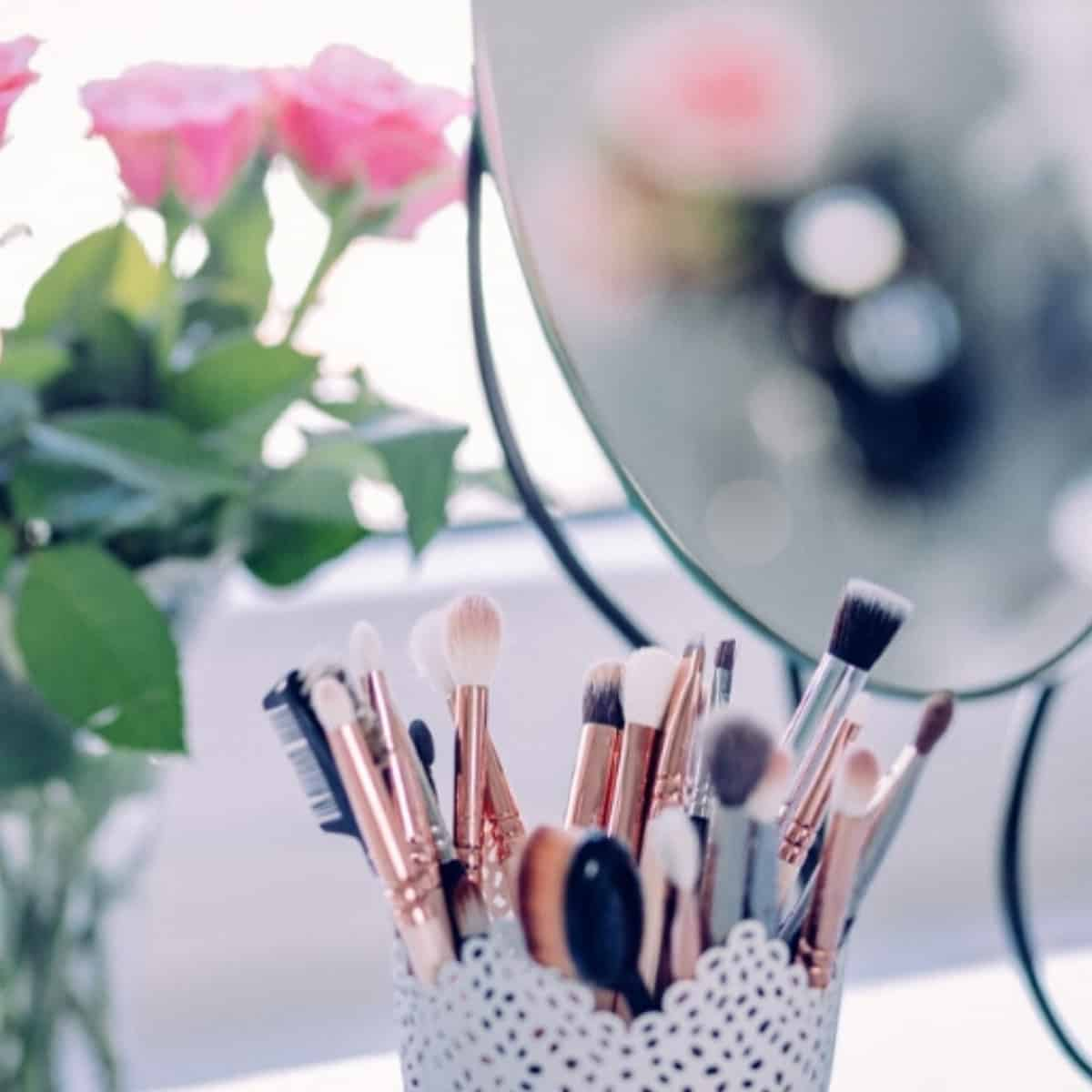 self care vanity table with makeup brushes and pink roses