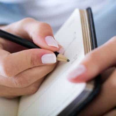 lady holding a notebook and pencil