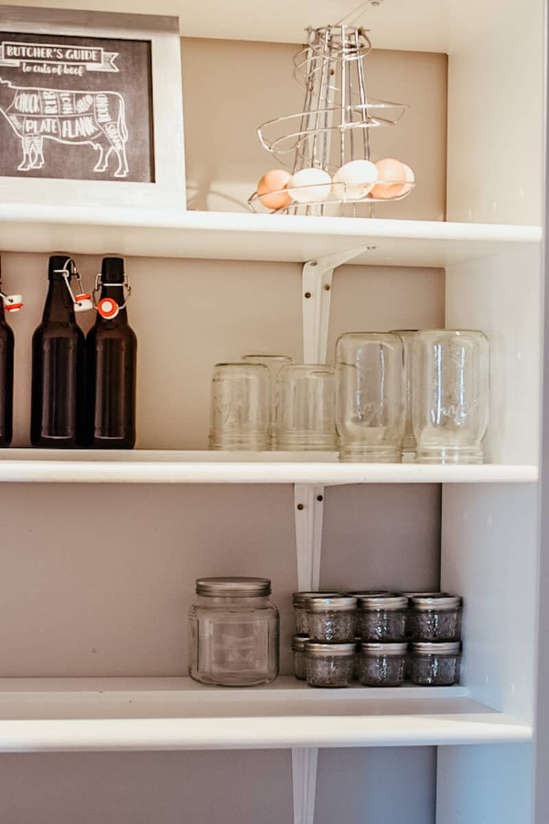 shelving in farmhouse pantry with empty mason jars
