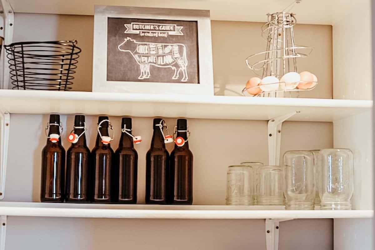 empty glass bottles on white pantry shelves