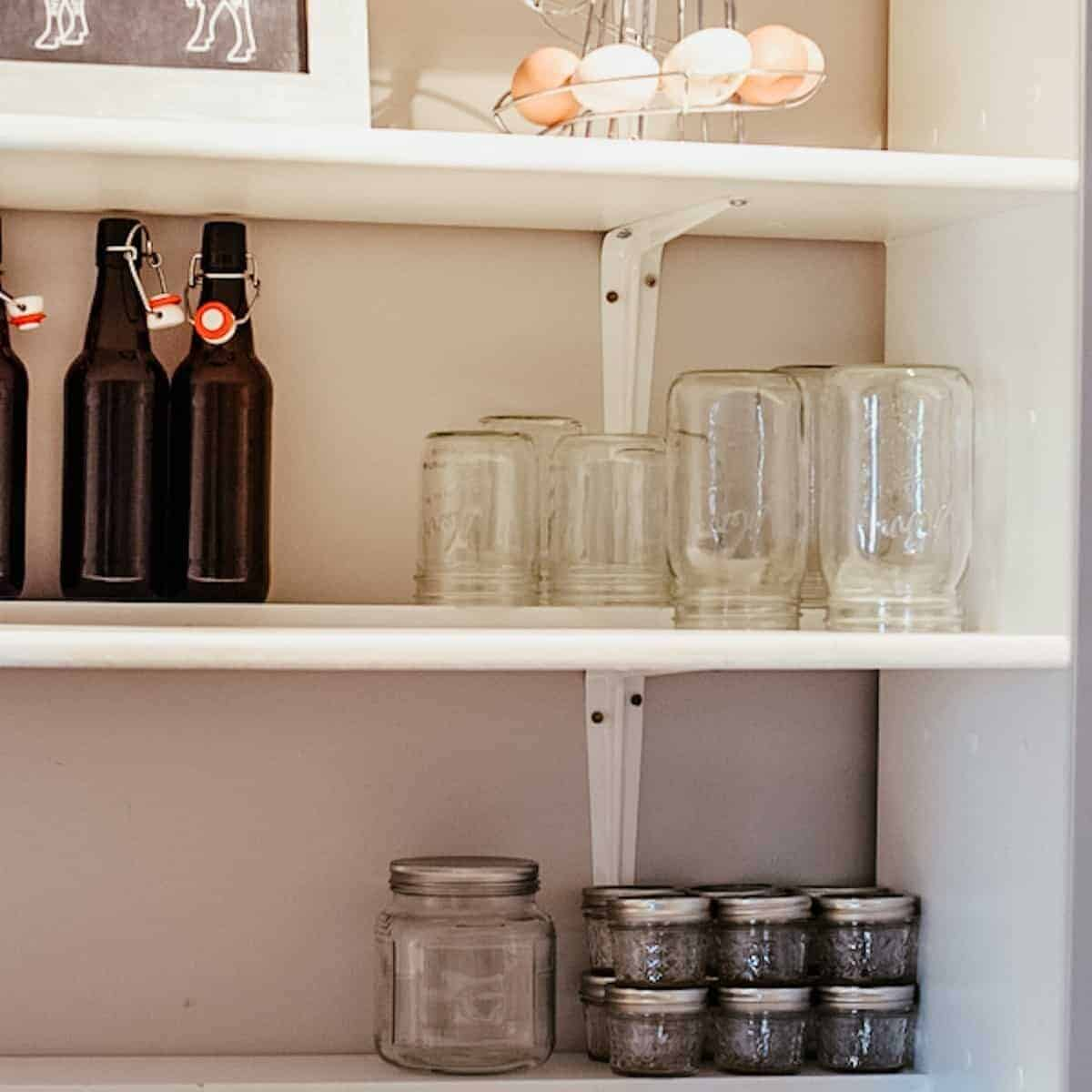 shelving in farmhouse pantry with empty mason jars and glass bottles
