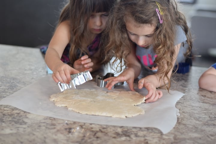 girls cutting out cookies with a cookie cutter