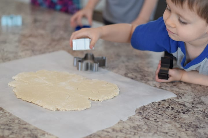 little boy helping cut out cookie shapes