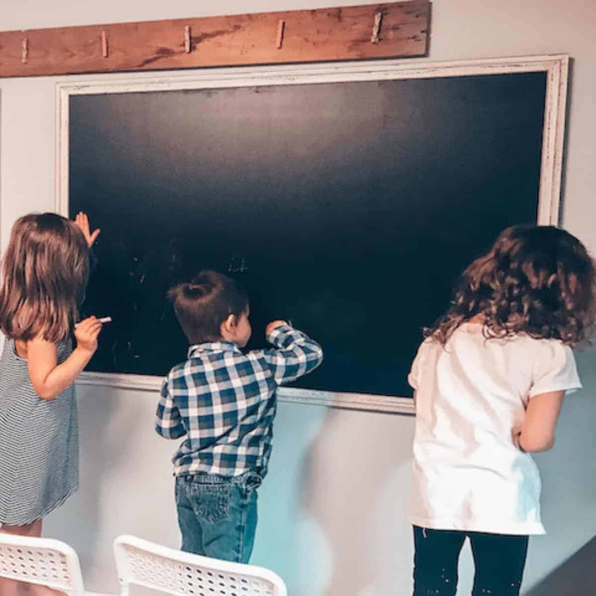 children writing on a chalkboard