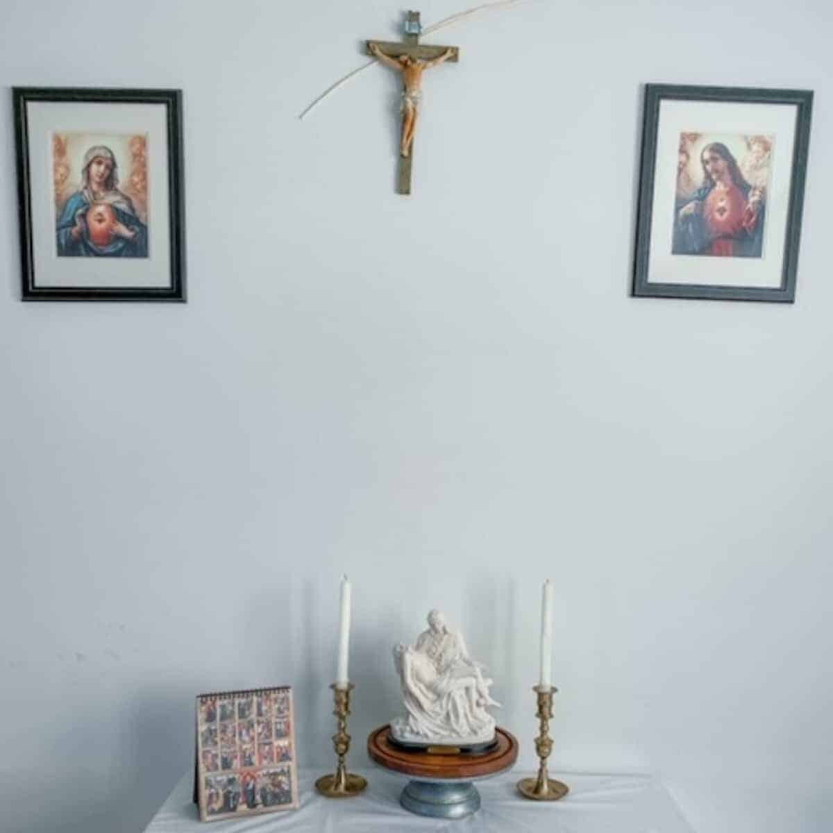 overview of the catholic home altar set up with statues, candles, and images