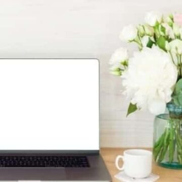 laptop on desk with a vase of white flowers and coffee cup