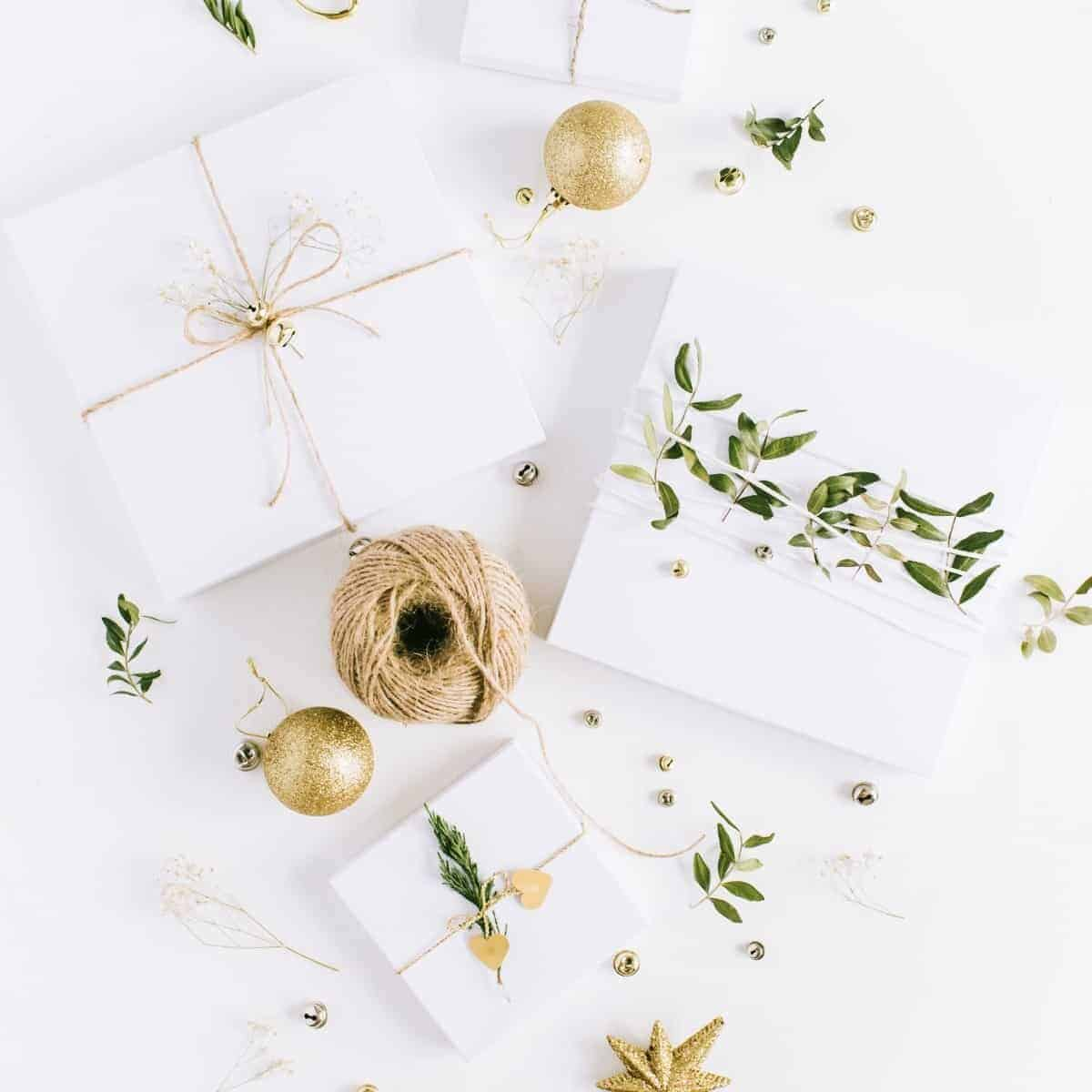stack of white gifts tied with twine and greenery