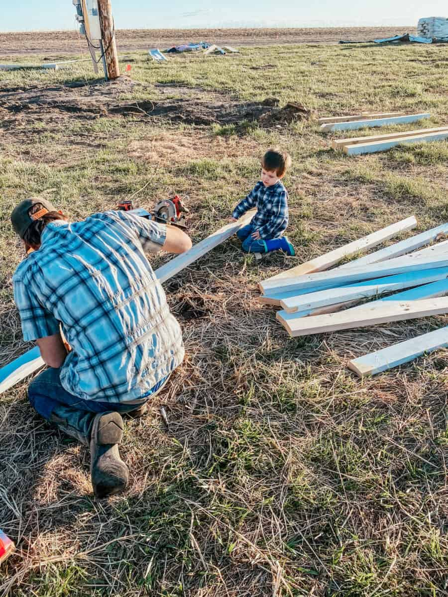father and son building with wood outside