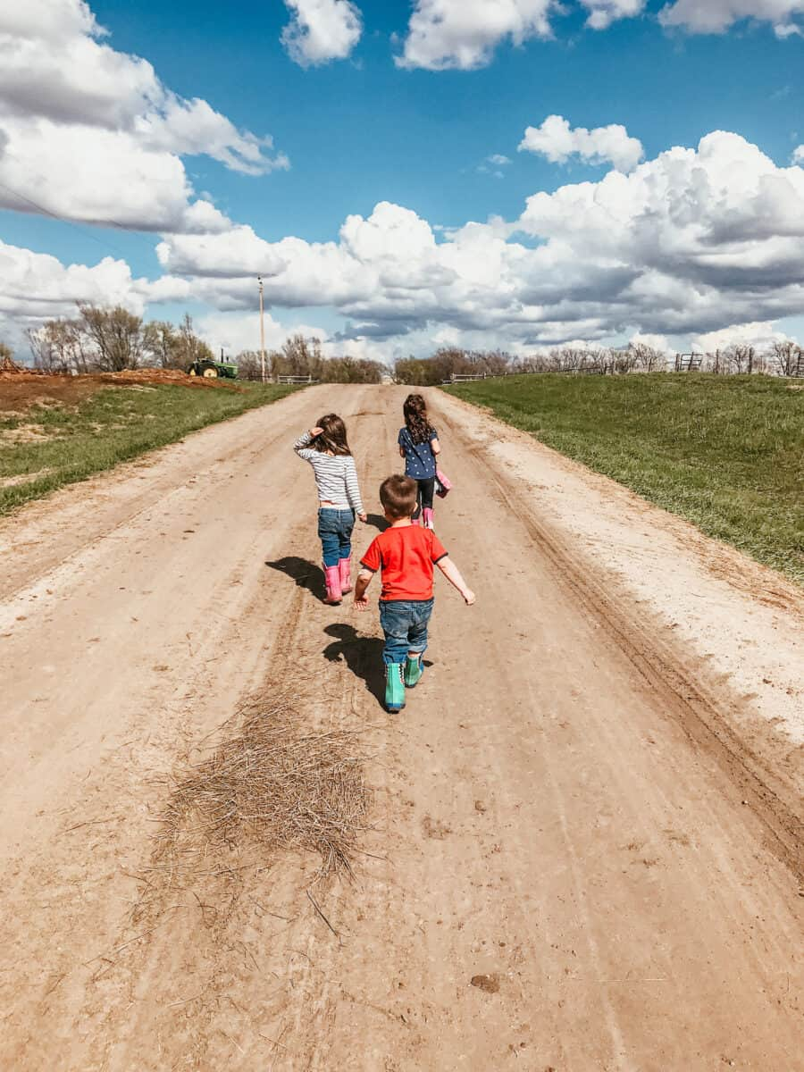 kids walking on a dirt road in the country
