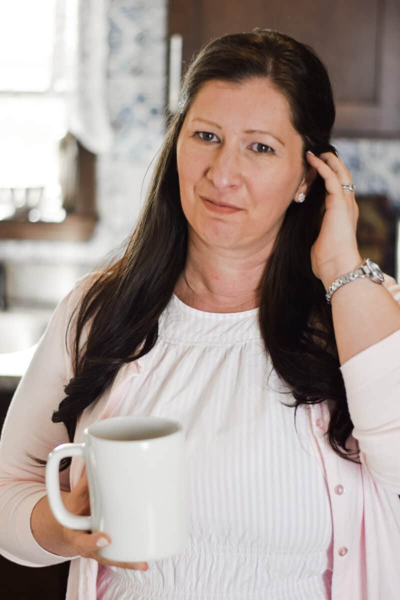 headshot of Mary in the kitchen with a cup of coffee