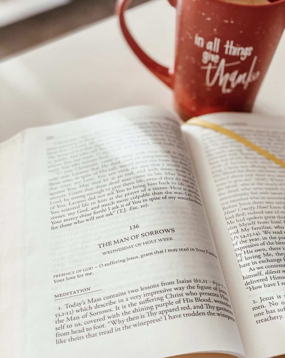Divine Intimacy book open with a coffee cup in the background