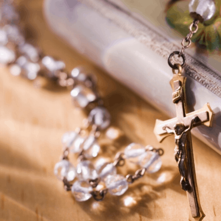clear rosary laying on a prayer book