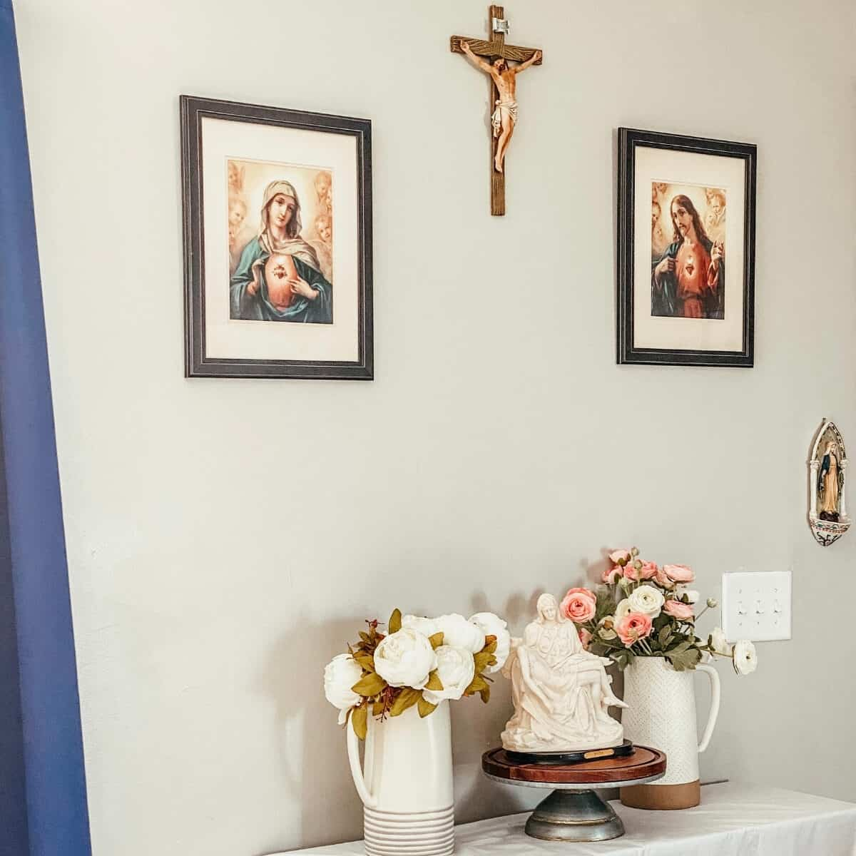 home altar with crucifix and Sacred & Immaculate heart frames above, two pitchers of white and pink flowers on each side