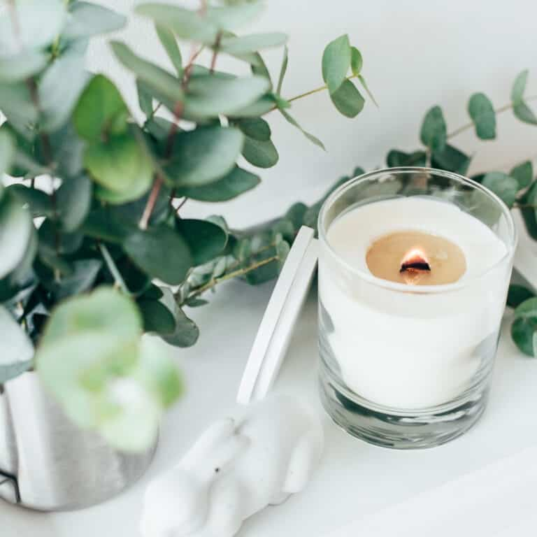 white candle in glass with eucalyptus leaves in background